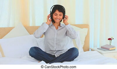 Casual asian lady listening to music mwith headphones