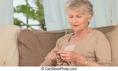 Retired woman knitting on her couch