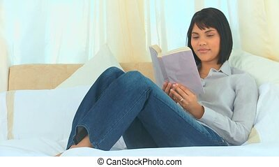Relaxed asian woman reading a book in the bedroom