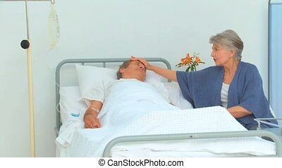 Woman paying her sick husband a visit at the hospital