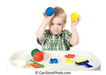 happy child playing with plasticine colorful balls
