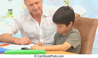 Grandfather helping his grandson to do his maths homeworks...