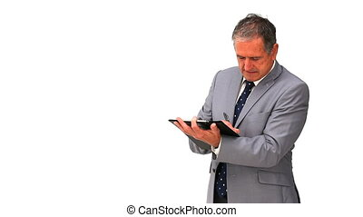 Mature businessman taking notes isolated on a white...