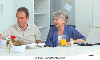 Retired couple taking the breakfast in the kitchen