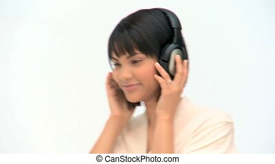 Lovely asian woman listening to music with headphones...
