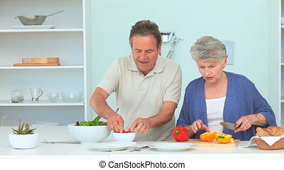 Cute mature couple preparing the dinner in the kitchen