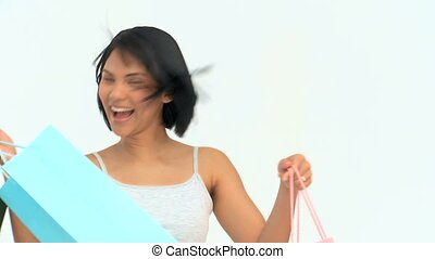Asian woman holding shopping bags isolated on a white...