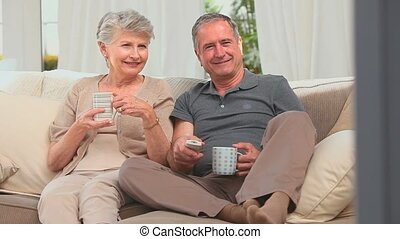 Lovely mature couple watching the tv in the living room