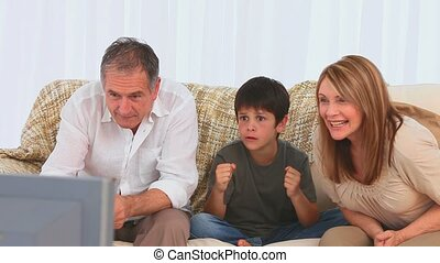 Family watching a match on the tv in the living room