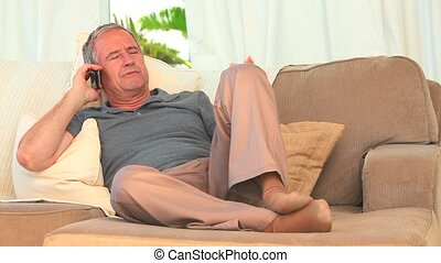 Middle aged man speaking on the phone on his sofa