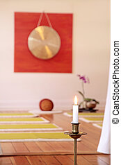 Large Gong, candle and orchid decoration in a yoga room