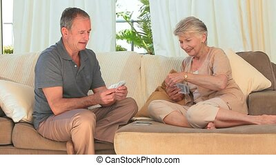 Elderly couple playing cards on the couch