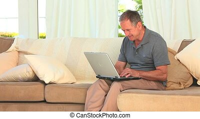 Middle aged man using a laptop on his couch