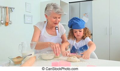 Adorable child learning to cook with her grandmother