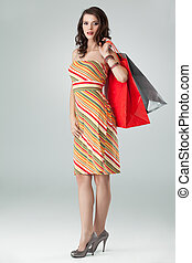 portrait of a young woman holding in one hand a few shopping bags and the other one on her hip. she is laughing and looking happy.