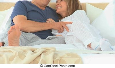 Cute elderly couple talking to each other on their bed