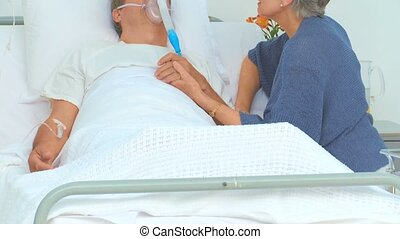 Elderly woman talking to her unconscious husband at the...