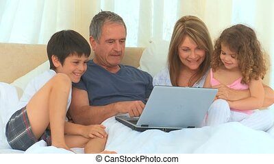 Family laughing in front of laptop on the bed