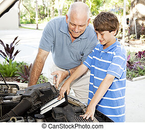 Family Car Repairs - Father shows his son how to put a clean...