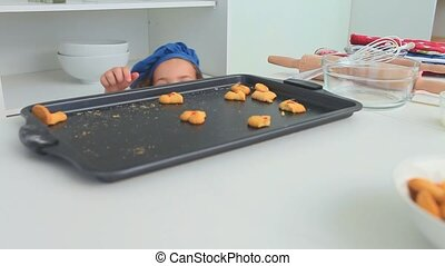 Little girl with a blue hat stealing cookies in the kitchen