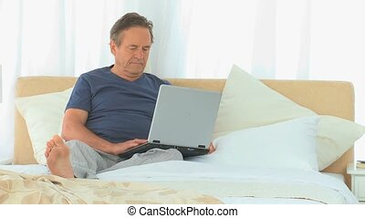 Mature man working on a laptop during the morning on his bed