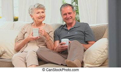 Middle aged couple watching tv