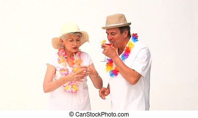 Lovely elderly couple in vacation drinking cocktails