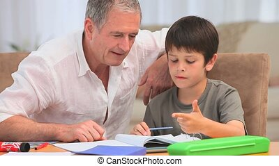 Little boy doing his maths homeworks with his grandfather