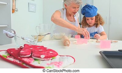 Grandmother taching to her grand daughter how to bake in the...
