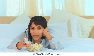 Good looking asian lady watching the tv with popcorn in the...