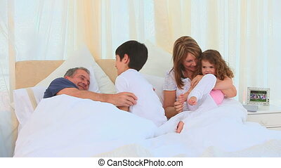 Children and their grandparents laughing on the bed