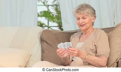 An elderly woman with cards in her hands in the living room