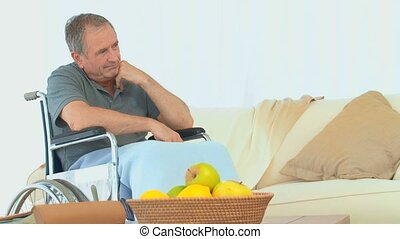 Sad man in a wheelchair thinking in the living room