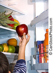 child taking the apple from the refrigerator