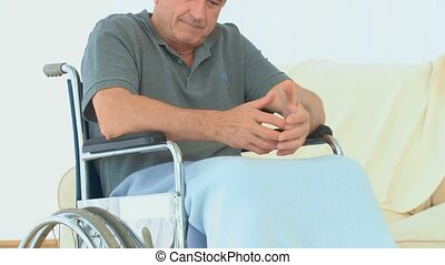 Man in a wheelchair looking at the camera in the living room
