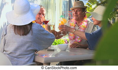 Elderly friends having an aperitif in vacation