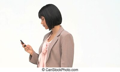 Serious businesswoman writing a sms on her phone against a...