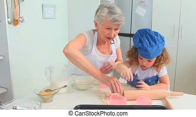 Grandmother and her granddaughter cooking together in the...