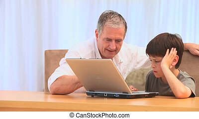 Grandfather with his grandson - Grandfather using a laptop...