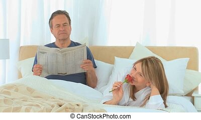 Aged couple during the morning on their bed