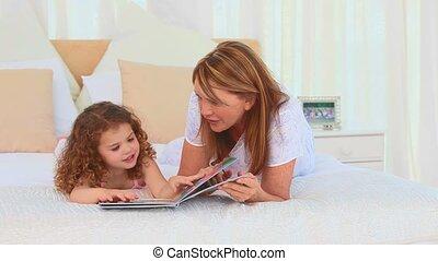 Lovely little girl reading a book