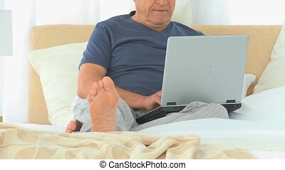 Retired man working on a laptop in his bedroom