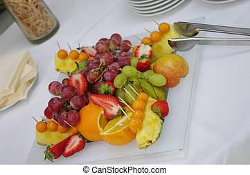 dish of fruit at table with white tablecloth