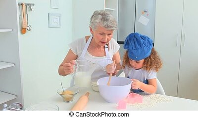 Adorable little child cooking with her grandmother