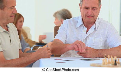 Two mature men playing cards in a nursing home