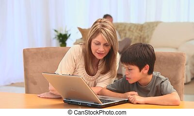 Grandmother with her grandson using a laptop in the living...