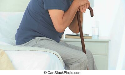 Happy mature man sitting on his bed