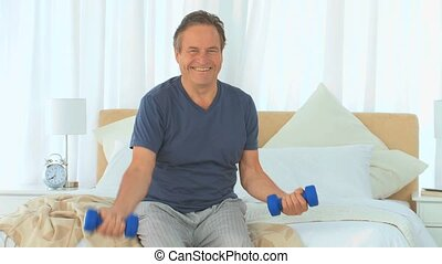 Dynamics man with dumbbells on her bed