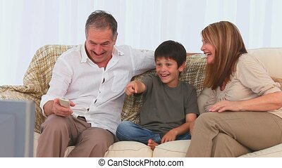 Cute family watching the tv on their sofa