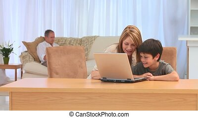 Grandmother and her grandson with a laptop in the living...